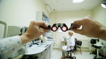 phoropter : Optical eyeglass frames close-up, ophthalmologist examining patient with optometrist trial frame, visual inspection device in ophthalmological clinic, Stock Footage