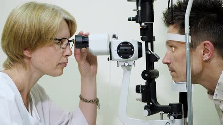 mérés : female doctor optometrist, ophthalmologist with non contact tonometer is cheking patients vision, intraocular pressure at eye clinic or optics store, ophthalmilogical laboratory.