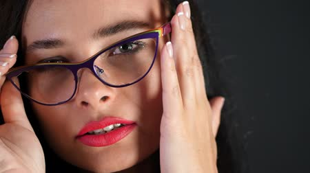 szemüveg : portrait of a sexy brunette woman with red lips who eroticly and playfully tries on stylish glasses, spectacles and looking sexually at camera in studio. dark gray background. Stock mozgókép