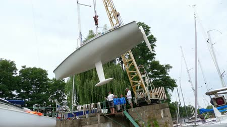zbourán : KYIV, UKRAINE, YACHTING-JULY 29, 2018: on the Dnieper River shore, on pier, a hoisting crane raises a white yacht. put on special fastenings, parking on the ground