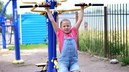 ginásio : smiling, happy eight year old girl engaged, doing exercises on outdoor exercise equipment, outdoors, in the park, summer, hot day during the holidays.