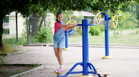 детская площадка : smiling, happy eight year old girl engaged, doing exercises on outdoor exercise equipment, outdoors, in the park, summer, hot day during the holidays.