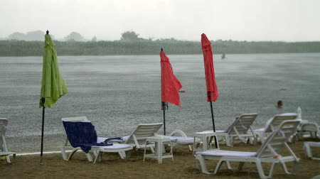 evacuation : summer rain, thunderstorm, heavy rainfall on an empty beach, by river. lonely empty sun loungers and beach umbrellas are standing, strong, gusty wind,