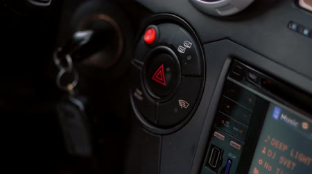 toggle : close-up, in the car, the drivers hand presses the emergency light