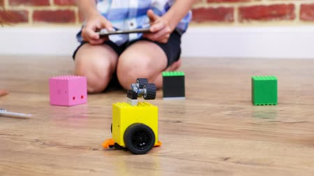 criar : close-up, radio-controlled robot moves on floor, little geniuses, children play electronic robots, cars, modern toys on radio control. new technologies in gaming industry.