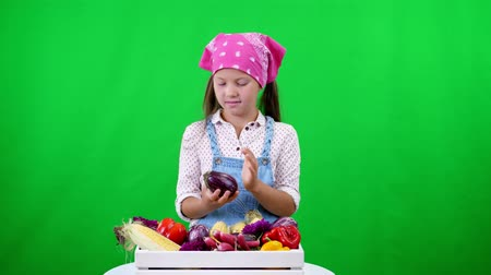 cachos : cute, smiling, little farmer girl shows a box with different fresh vegetables, harvest. on green background in studio. Healthy food to your table, Healthy nutrition.