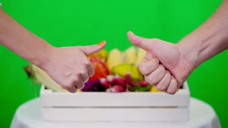 idéia genial : close-up, Two hands showing thumbs up sign, Ok sign, against Chromakey, green background and a box full of different vegetables, in studio. concept of crop counting, harvest of vegetables