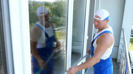 utírat : Caucasian handsome man, worker of cleaning service, in blue overalls and in a cap, blaser, Cleaning, washing Windows by special mop, enjoying his work. Dostupné videozáznamy