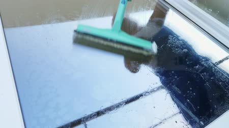 limpador : close-up, in the window glass is reflected a man, worker of cleaning service, in blue overalls and in a cap, blaser, Cleaning, washing Windows by special mop,