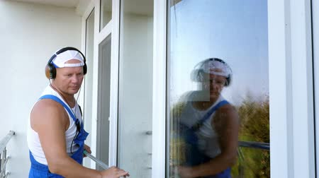 szobalány : Caucasian attractive man, cleaning service worker, in blue overalls, listening to music on mobile phone with headphones , Cleaning, washing Window by special mop, Stock mozgókép
