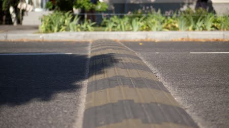 factor : close-up, cars cross special restraint on the road, Traffic safety speed bump on an asphalt road, Stock Footage
