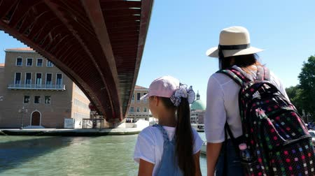 east pearl : VENICE, ITALY - JULY 7, 2018: on a hot summer day, tourists, woman in hat and sunglasses, and an eight-year-old girl, admiring the views of Venice, standing under the bridge Stock Footage