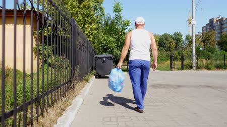 recusar : back view, man is carrying a package of garbage in his hands, take out trash. summer hot day. ecology. separation of debris, cleanliness of the environment