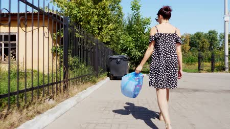 újrahasznosított : back view, girl is carrying a package of garbage in her hands, throwing out trash. summer hot day. ecology. separation of debris, cleanliness of the environment