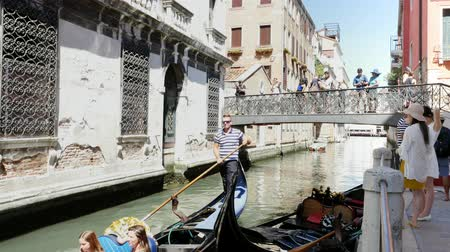 venetian lagoon : VENICE, ITALY - JULY 7, 2018: narrow canal between the ancient houses of Venzia, hot summer day. traditional Venetian gondola floats along the canal, carries tourists