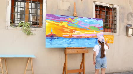 expressionism : VENICE, ITALY - JULY 7, 2018: girl child in shorts and a cap examines a bright picture on the street of Venice, on a hot summer day. Stock Footage