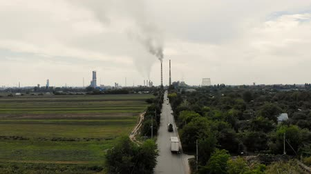 pipe tube : aero. in middle of field, a road with cars that leads to a large plant, two tall, big, smoking chimneys. gray smoke comes out of the pipes. ecology, pollution of the environment. Stock Footage