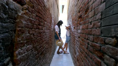 grande : VENICE, ITALY - JULY 7, 2018: in very narrow street of Venice, between old houses walls, stand a teenager girl, child and young woman, in shorts and hats. summer hot day.