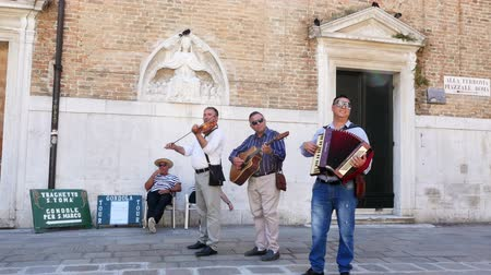 tambourine : VENICE, ITALY - JULY 7, 2018: street musicians, trio, playing on the street of Venice, entertains tourists