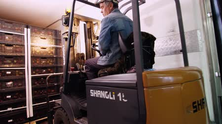 rukojeť : loading of a truck. a worker on a small auto-loader, Electric forklift truck imports, loads boxes of apples into a large truck van, in warehouse. Warehouse man works with forklift.