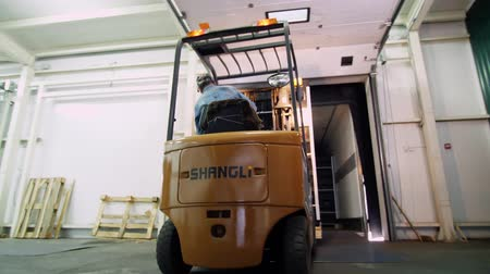 empilhamento : loading of a truck. a worker on a small auto-loader, Electric forklift truck imports, loads boxes of apples into a large truck van, in warehouse. Warehouse man works with forklift.