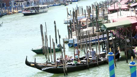 estreito : VENICE, ITALY - JULY 7, 2018: gondoliers are waiting for tourists on special piers, stops for gondolas. Grand Canal , hot summer day.