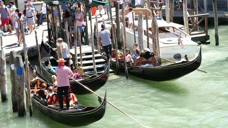 estreito : VENICE, ITALY - JULY 7, 2018: Grand Canal , gondolas full of tourists. gondoliers are waiting for tourists on special piers, stops for gondolas. hot summer day.