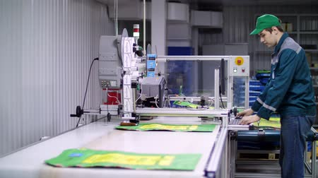 tek bir nesne : worker of printing equipment, adjusts, regulates the printing process. working process of printing packages for grain, agricultural products. Conveyor belt. The work of modern printing equipment Stok Video