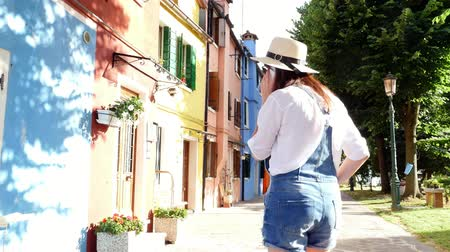 burano : VENICE, BURANO, ITALY - JULY 7, 2018: young woman, girl in sun glasses, hat, shorts, talking on the phone, smiling. Burano Island with multicolor houses, near Venice.