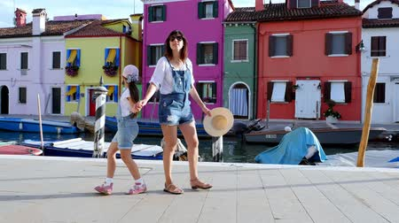 arenito : VENICE, BURANO, ITALY - JULY 7, 2018: a young woman and a kid girl in identical denim overalls, shorts, walk through the streets, along the small canal of Burano. summer hot day.