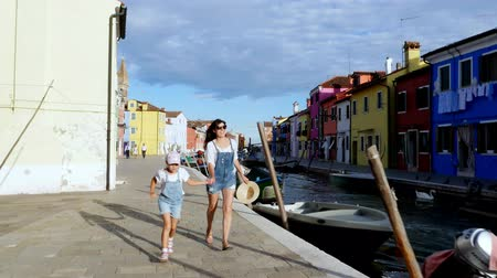 arenito : VENICE, BURANO, ITALY - JULY 7, 2018: a young woman and a kid girl in identical denim overalls, shorts, run along the small canal of Burano. summer hot day. Stock Footage