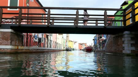 burano : VENICE, BURANO, ITALY - JULY 7, 2018: Bridge and canal with colorful architecture on the famous island Burano. Many colorful houses, boats along a small canal. Stock Footage
