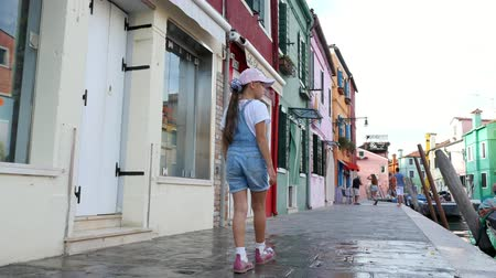 burano : VENICE, BURANO, ITALY - JULY 7, 2018: pretty kid girl in blue denim overalls, shorts, and cap, walks through the streets, along the small canal of Burano. summer hot day.