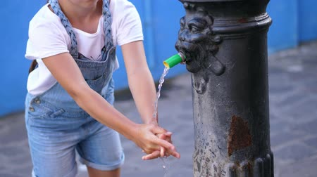 externo : Crystal clear water flows from an old Public Iron Fountain , a well, kid girl washes her hands under a stream of water. close up Vídeos