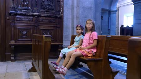 rahip : OROPA, BIELLA, ITALY - JULY 7, 2018: children are sitting on a bench in a catholic old church, looking at wall paintings. Shrine of Oropa, Sanctuary, in the mountains near the city of Biella, Piedmont, Italy. Stok Video