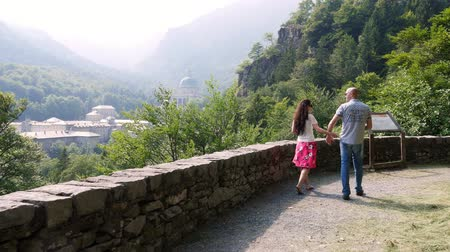madona : OROPA, BIELLA, ITALY - JULY 7, 2018: beautiful couple man and woman walking in park in mountains, near Shrine of Oropa, Sanctuary, Sacro monte della beata Vergine, located in the mountains near the city of Biella, Piedmont, Italy.