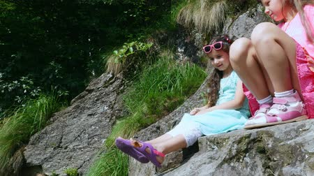 мотылек : two pretty girls, kids, sit on a ledge in the rock., a beautiful orange mountain butterfly whirls and flies over a childs leg in sandals. butterfly sits on the foot. summer hot day