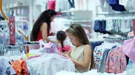 grocery store : shopping in the store. childrens clothing department. girl, kid, chooses things in the store. Little fashion-girl. little shopaholic. tedious shopping in stores, shops