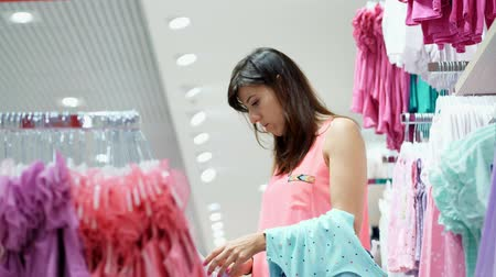 awaiting : shopping in the store, shopping. childrens clothing department. young woman, mother chooses things for her child. Stock Footage