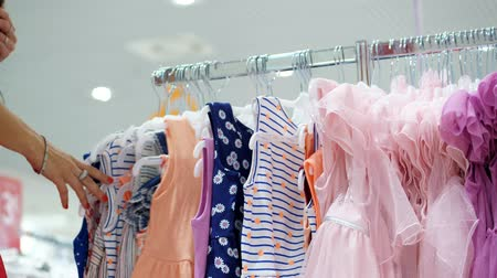 usado : close-up, female hands sorted out many hangers with outfits. selection and purchase of clothes in the store. shopping. shopaholic. Dresses hanged in a clothing store