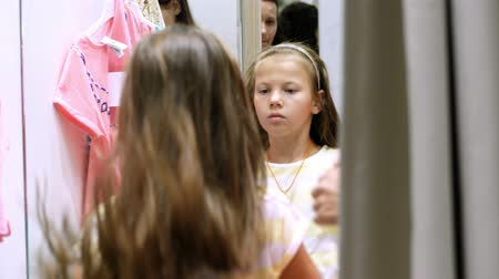 fashion outlet : shopping. in fitting room of large store, pretty, serious girl, a kid tries on new outfits, chooses what to buy. The reflection in mirror. childrens clothing department. Little fashion-girl.