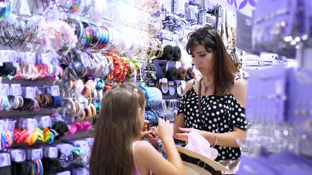 gumka : womans hair accessories in shopping mall. girl, kid and mum choose hairpins, rubber bands, hair band, in the store.