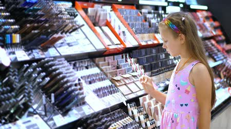 tester : cosmetics shop, pretty girl, kid, carefully considers cosmetic products, in beauty store. Little fashion-girl