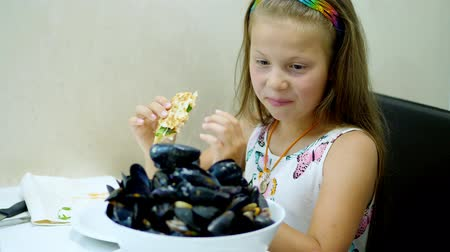 midye : Close-up, in the restaurant, the kid girl served on the table a large bowl, a plate of cooked open blue mussels. child very happy. large portion of yummy, delicacy