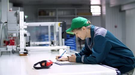 připomínka : elderly woman, employee, worker at an enterprise, factory, fills up a service journal, record book, working industrial background.