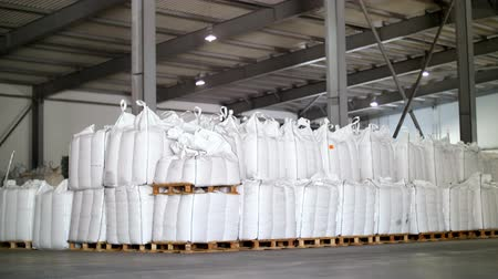 forklift : large, full bags of cereal products in stock. The bags are stacked in rows, industrial warehouse