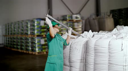 javelin : CHERKASY, UKRAINE - AUGUST 24, 2018: woman, employee of agricultural enterprise, takes samples of corn grain from big bags in warehouse for analysis in lab. Stock Footage