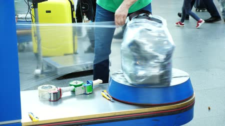 motivo : Luggage wrapping service in airport for security reason and safety protection from damage.