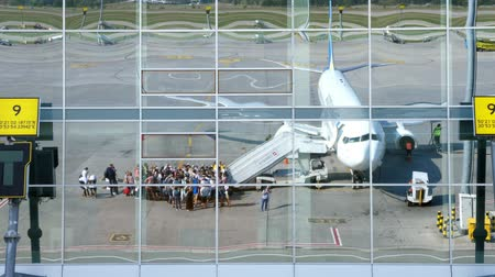 bilet : AIRPORT BORYSPIL, UKRAINE - OCTOBER 24, 2018: Ukraine International Airlines. passengers Boarding on flight and get ready to flight. reflection in mirrored windows of airport building. summer sunny day