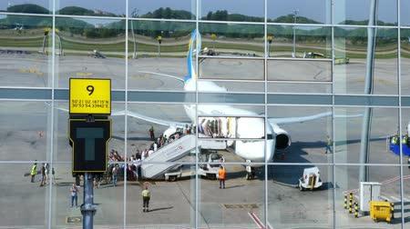 bilet : AIRPORT BORYSPIL, UKRAINE - OCTOBER 24, 2018: Ukraine International Airlines. passengers Boarding the plane and get ready to flight. reflection in mirrored windows of airport building. summer sunny day